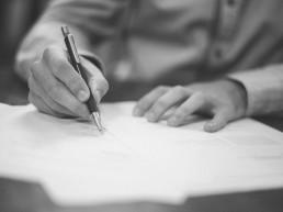 Rechtsanwalt Prelinger Aufsätze - Hände schreiben auf Papier